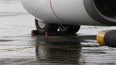 chock : Chocked wheels of airplane undercarriage and part of jet engine under heavy rain