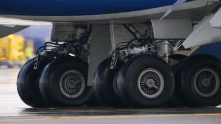 construir : Wheels of aircraft undercarriage. Close up of taxiing airplane landing gear Stock Footage
