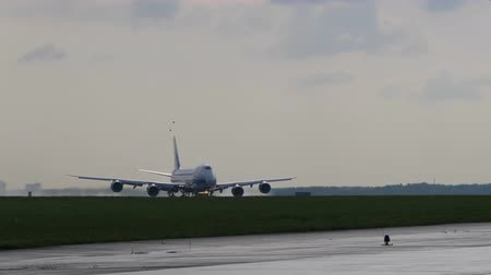 aerodrome : Takeoff run of Jumbo Jet. Cargo aircraft takes off from runway against cloudy sky