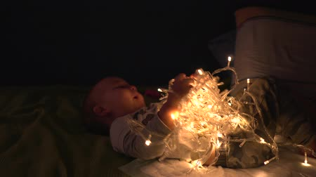 změť : Happy baby boy play with tangled LED garland shining in different modes