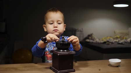 Baby boy puts coffee beans into wooden vintage hand grinder