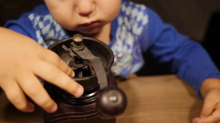 Cute baby boy touches vintage coffee mill with his little fingers