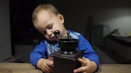 Baby pulls a box out of vintage hand coffee mill and throw out brown beans