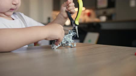 Serious little baby boy repairs meccano construction with needle-nose pliers
