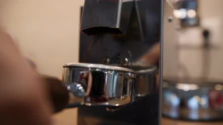Ground coffee pours from modern grinder into filter holder. Close up shot Стоковые видеозаписи