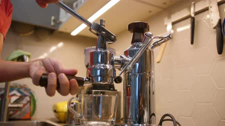 Man sets filte holder in modern steel coffee machine for preparing a cup of morning beverage Stok Video