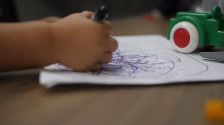 Close up of childs hands drawing scribblings with a soft-tip marker on white paper Stok Video