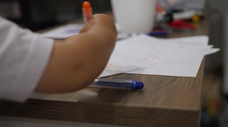 Close up shot of drawing kid. Baby scribblings made with orange marker Stok Video