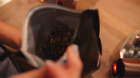 Full packet of coffee beans. Woman shakes just opened pack. Close up shot