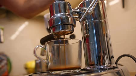 Filter of coffee machine and hot beverage pouring through it unto mug. Low angle view