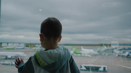 Little boy in airport looks on support vehicles and cloudy sky through window
