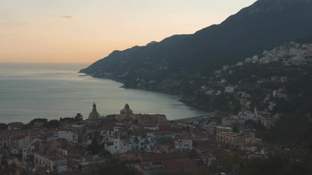 amalfitana : Sunset over Italian coastal town. Panoramic view of buildings on hills along sea shore