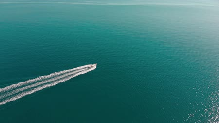 Motor boat floats in endless blue sea. Rippling water shine in the sun. Aerial shot