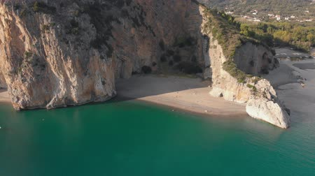 Sandy beach between steep rocks. Mediterranean coastline in sunny day. Aerial, camera moves away