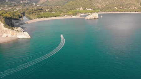 Motor boat floats towards river mouth at woody coastline. Aerial shot of sea shore. Campania, Italy Stok Video