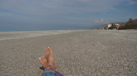 Bare feet of woman lying on pebble beach. Rest near the sea on sunny day. First person view