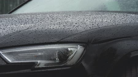 Rain drops fall on a black car. Close up shot of auto bonnet and headlight
