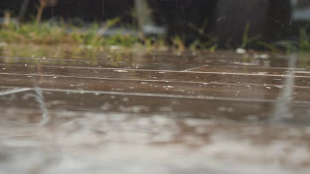 Rain drops fall on the wooden floor. Close up shot of splashes from heavy rain