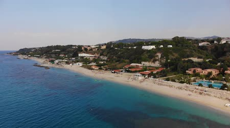Sandy beach with hotels and resorts. Aerial view of azure sea and hilly coastline of Italy