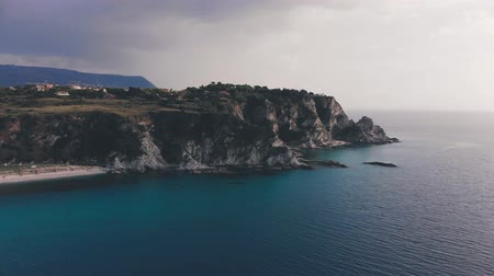 Dark rain cloud over rough rocky cape and turquoise sea waters. Aerial shot of Capo Vaticano cliff, Italy