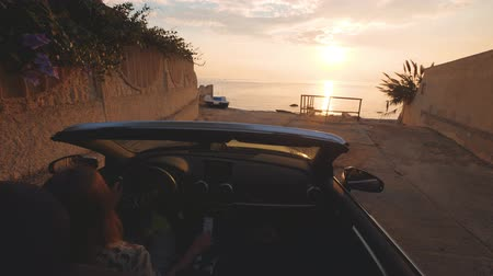 Woman parks cabriolet car near a beach for looking on beautiful sunset over sea