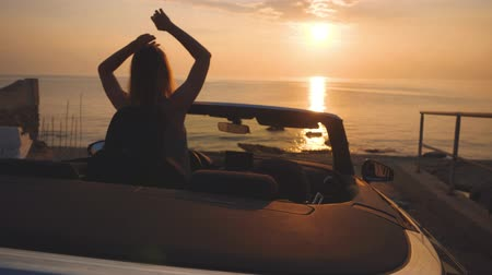 Dancing woman shakes hair. Luxury convertible car parked near sunset beach