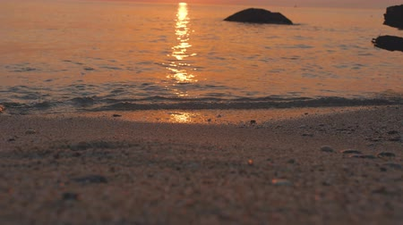Sea waves roll on sandy beach. Sunset shines on water surface with yellow and orange Stok Video