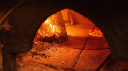 ralado : Burning fire in stone oven and pizza is baked near it. Traditional italian cuisine