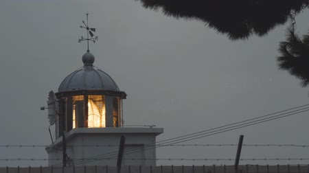 lapát : Lighthouse emits beam of light shining through rain drops. Bad weather at sea shore