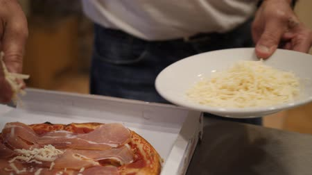 Mature man strews grated hard cheese on a hot pizza in take out box. Close up shot Стоковые видеозаписи