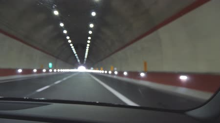 Car rides through the tunnel towards the light in the end. Unfocused POV shot
