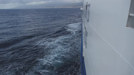Side of large ferry boat, bow waves on dark blue sea and coastal town on horizon Stok Video