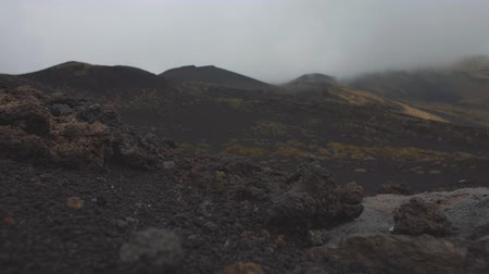 Black stones on lifless volcano slopes. Low gray clouds covere mountain top