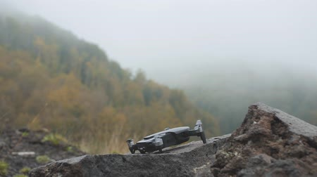 Drone takes off from rough stone in misty mountains. Fog in autumn forest. Handheld shot