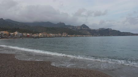 Hilly coastline. View on Taormina city from a beach. Clouds on mountain top