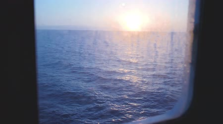 Sunrise above the blue sea. View from ferry boat porthole on waves reflecting sun light