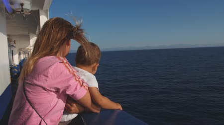 Mother with baby at the deck of ferry boat floating in blue sea. Windy sunny day