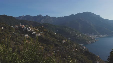 Lattari mountains over blue sea. Morning on hilly coast with trees and houses. Panning shot