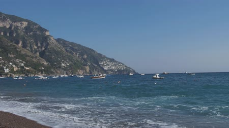 Swimming people and floating watercrafts at sea beach in Positano, Amalfi coast, Italy Stok Video