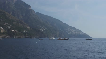 amalfi coast : Floating in blue sea among motor boats. Town on steep slopes of hilly coastline