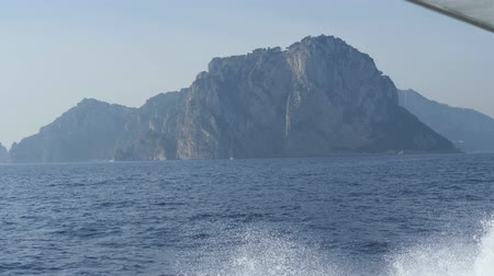 Steep cliff on shores of Capri. Mountain over blue sea. Boat comes up to island. Monte Tiberio, Italy Stok Video