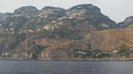 Floating along rocky mountain on sea shore. Hillside houses on steep slopes Стоковые видеозаписи