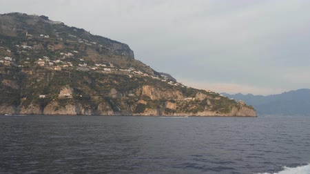 Coastal mountain with hillside village. Motor boat floats along rocky sea shore, Italy