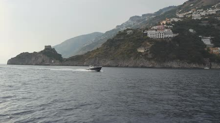 Modern fast motor boat floats along hilly shore of Sorrento Peninsula, Italy Stok Video