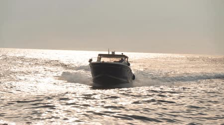 endless gold : Modern motorboat moves fast on waves. Sea water reflects sunlight and shine Stock Footage