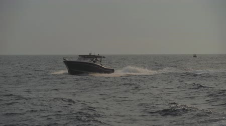 Small black motor boat floats on sea waves leaving white foam track