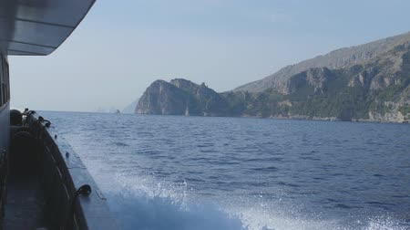 positano : Motor boat moves along mountainous sea shore. View from deck in white splashes Stock Footage