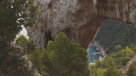 arco : Natural arch in rocks high above the sea shore. Panning vew. Capri, Italy