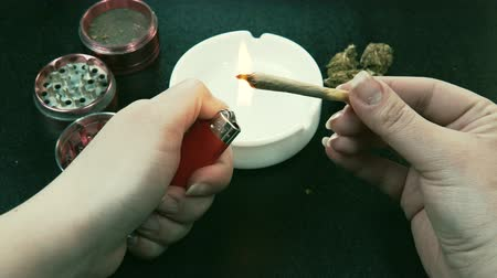 Smoking medical marijuana joint. Marijuana buds, grinder and ashtray on the background. Joint in the female hand