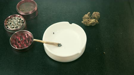 курильщик : Stock video Smoking medical marijuana joint. Marijuana buds, grinder and ashtray on the background. Joint in the female hand